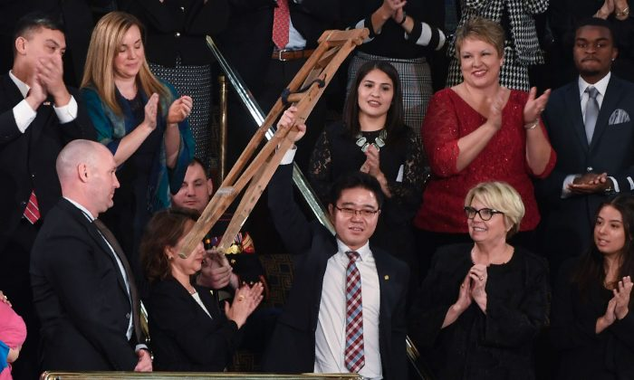 North Korean defector Ji Seong Ho raises his crutches as President Donald Trump delivers the State of the Union address in Washington, on Jan. 30, 2018. (SAUL LOEB/AFP/Getty Images)