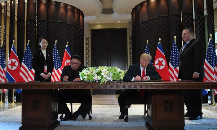 President Donald Trump and North Korea's leader Kim Jong Un sign documents as Secretary of State Mike Pompeo (R) and Kim's sister Kim Yo Jong (L) look on at a signing ceremony during their historic US-North Korea summit, at the Capella Hotel on Sentosa Island in Singapore on June 12, 2018. (SAUL LOEB/AFP/Getty Images)