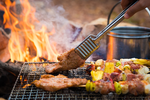 Close up grilling barbecue in the campground at summer camp travel, Skewers of pork and beef fillet on barbecue party in camping.(Getty Image)