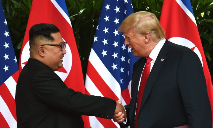 North Korean leader Kim Jong Un (L) shakes hands with U.S. President Donald Trump (R) after taking part in a signing ceremony at the end of their historic U.S.-North Korea summit, at the Capella Hotel on Sentosa Island in Singapore on June 12, 2018. (ANTHONY WALLACE/AFP/Getty Images)