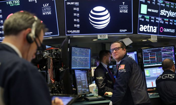With a logo and trading information for AT&T behind them, traders and financial professionals work ahead of the closing bell on the floor of the New York Stock Exchange (NYSE) in New York City on June 13, 2018. (Drew Angerer/Getty Images)