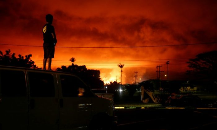 Darryl Sumiki, 52, of Hilo, watches as lava lights up the sky above Pahoa during ongoing eruptions of the Kilauea Volcano in Hawaii, on June 2, 2018. (Terray Sylvester/Reuters)