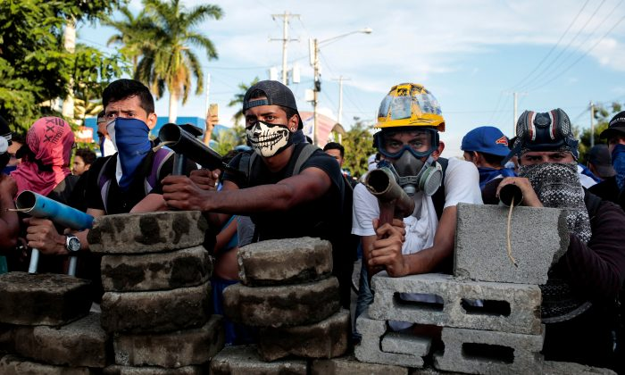Demonstrators stand behind a barricade during clashes with riot police during a protest against Nicaragua's President Daniel Ortega's government in Managua, Nicaragua May 30, 2018. (Reuters/Oswaldo Rivas)