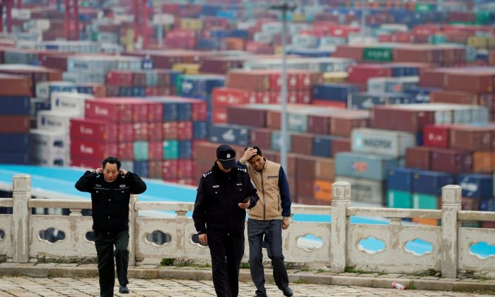 Security guards walk in front of containers at the Yangshan Deep Water Port in Shanghai, China on April 24, 2018. (Aly Song/File Photo/Reuters)