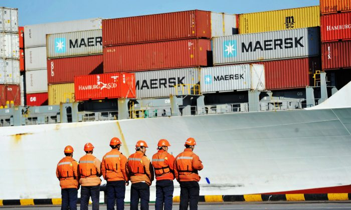 Workers stand in line next to a container ship in the Port of Qingdao, Shandong Province.(AFP/Getty Images)
