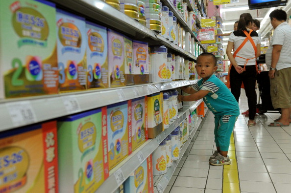 A baby plays around in the imported baby products section while his parents talk to a sales clerk in a supermarket in Beijing in 2013. (STR/AFP/Getty Images)