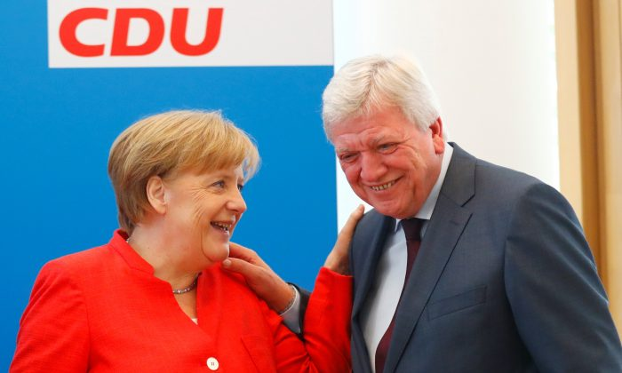 German Chancellor Angela Merkel and Volker Bouffier react as they attend the board meeting of Germany's Christian Democratic Union (CDU) in Berlin, Germany, June 18 2018. (Reuters/Hannibal Hanschke)