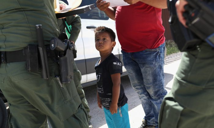 Border Patrol agents take into custody a father and son from Honduras near the U.S.-Mexico border by Mission, Texas, on June 12, 2018. The asylum seekers were then sent to a Customs and Border Protection processing center for possible separation. (John Moore/Getty Images)