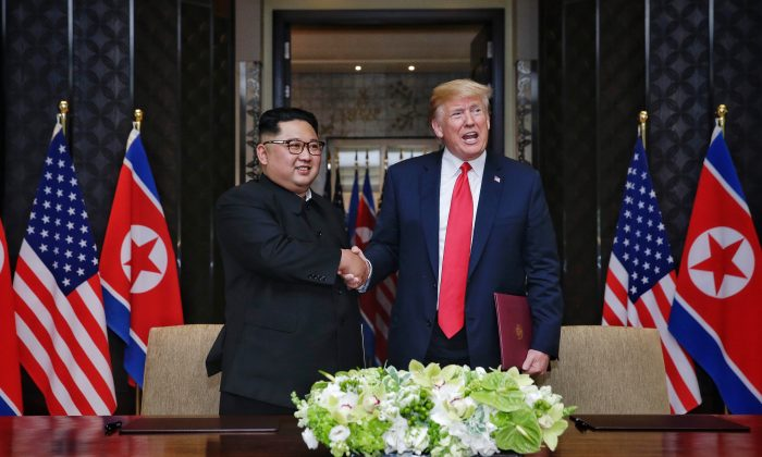 In this handout photograph provided by The Strait Times, North Korean leader Kim Jong-un (L) with U.S. President Donald Trump (R) during their historic U.S.-DPRK summit at the Capella Hotel on Sentosa island on June 12, 2018 in Singapore. (Kevin Lim/The Strait Times/Handout/Getty Images)