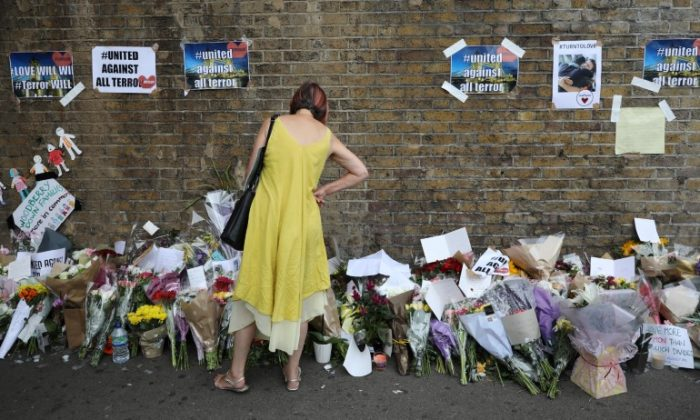 A woman looks at messages at the base of a wall near the scene of an attack next to Finsbury Park Mosque, in north London, Britain June 20, 2017. (Reuters/Marko Djurica)