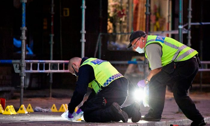 Policemen search the scene after three were shot dead and another three were injured in a shooting in the center  Swedish city of Malmo on June 18, 2018. (Johan Nilsson/AFP/Getty Images)