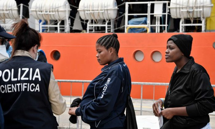 A Nigerian woman (2nd L) and other migrants disembark from the MV Aquarius upon its arrival at the Sicilian port of Messina, on May 14, 2018. (Louisa Gouliamaki/AFP/Getty Images)