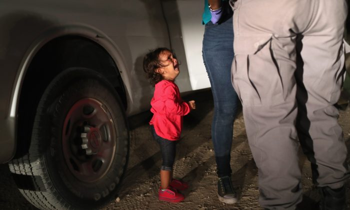 A two-year-old Honduran asylum seeker cries as her mother is searched and detained near the U.S.-Mexico border in McAllen, Texas, on June 12, 2018. (John Moore/Getty Images)