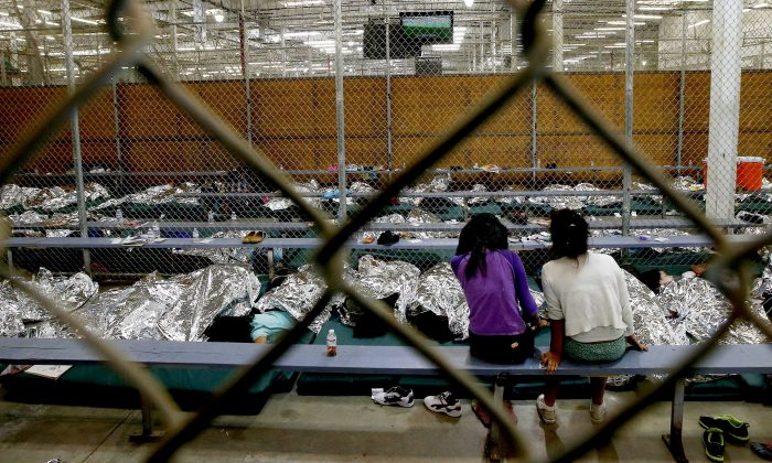 Two young girls sit in a holding area where hundreds of mostly Central American immigrant children are being processed and held at the U.S. Customs and Border Protection Nogales Placement Center on June 18, 2014, in Nogales, Arizona.  (Ross D. Franklin-Pool/Getty Images)