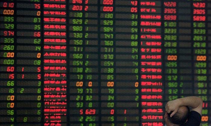 An investor monitors screens showing stock market movements at a brokerage house in Shanghai, on Sept. 1, 2015. (Johannes Eisele/AFP/Getty Images)