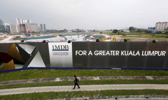A man walks past a 1 Malaysia Development Berhad (1MDB) billboard at the funds flagship Tun Razak Exchange development in Kuala Lumpur, March 1, 2015. (Reuters/Olivia Harris/File Photo)