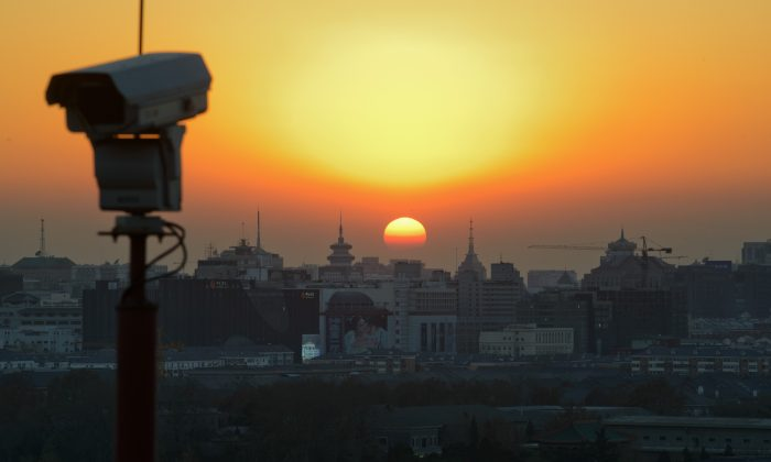 The sun sets behind the Beijing skyline and a security camera, on Dec. 5, 2013. (Ed Jones/AFP/Getty Images)