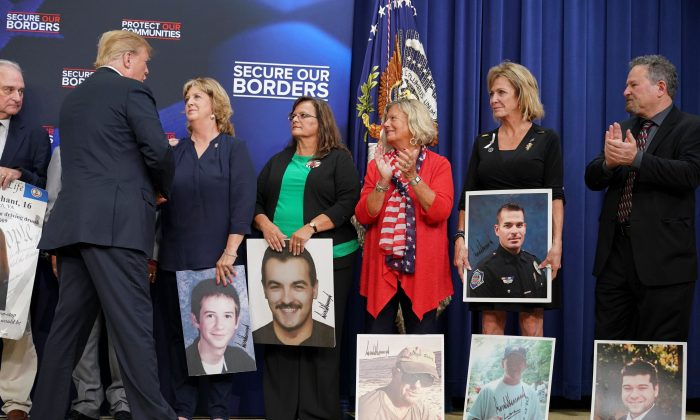 President Donald Trump greets people holding posters of their relatives who were killed by illegal immigrants, at the Eisenhower Executive Office Building in Washington on June 22, 2018. (MANDEL NGAN/AFP/Getty Images)