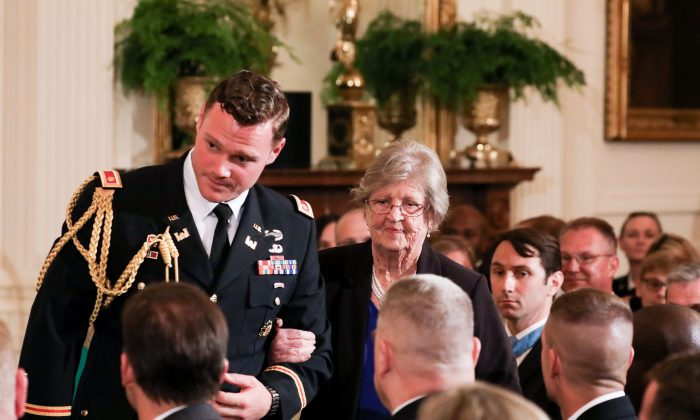 A military aide accompanies Pauline Conner as she arrives to be presented with the Medal of Honor to her late husband and 1st Lt. Garlin M. Conner by President Donald Trump in the East Room of the White House on June 26, 2018. (Samira Bouaou/The Epoch Times)