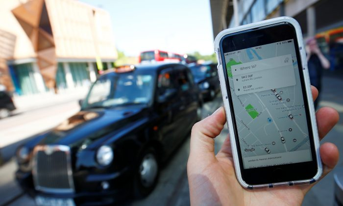 A photo illustration shows the Uber app on the mobile phone and a black cab in London, United Kingdom, June 25, 2018. (Reuters/Henry Nicholls/Illustration)