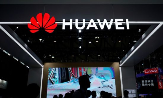 People walk past a sign board of Huawei at CES (Consumer Electronics Show) Asia 2018 in Shanghai, China June 14, 2018. (Reuters/Aly Song)