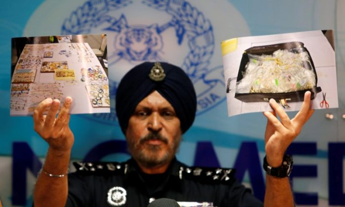 Amar Singh, head of Malaysia's Commercial Crime Investigation Department (CCID), displays photos of items from a raid during a news conference in Kuala Lumpur, Malaysia June 27, 2018. (Reuters/Lai Seng Sin)