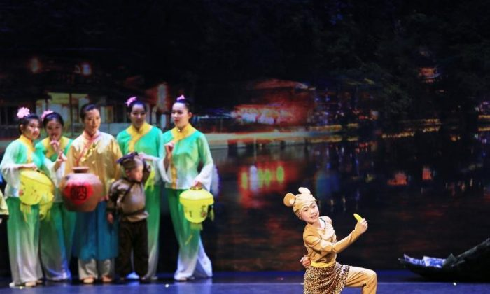 In Act One of Xian Yun's year-end production, the young Monkey King, played by 11-year-old Alyssa Li, is born from a rock while people celebrate a festival. (Courtesy of Xunqing Li/Xian Yun Academy)