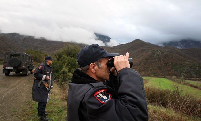 Albanian police officers patrol at the Albanian-Greek border in Carshove near the city of Permet on March 15, 2016.