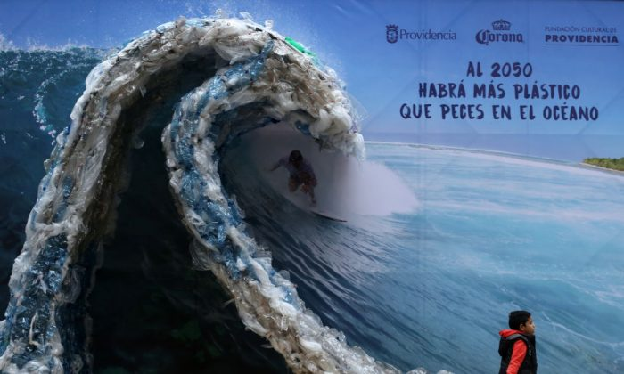 TOPSHOT - A billboard portraiting a man, surfing a wave made out of plastic bags and bottles, to denounce ocean's pollution is pictured in Santiago on the eve of the World Environment Day, on June 4, 2018.     (Photo credit should read CLAUDIO REYES/AFP/Getty Images)