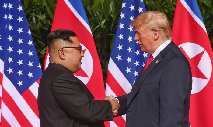 In this handout photo, North Korean leader Kim Jong-un (L) shakes hands with U.S. President Donald Trump during their historic U.S.-DPRK summit at the Capella Hotel on Sentosa island on June 12, 2018 in Singapore. (Photo by Handout/Getty Images)