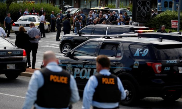 Law enforcement officials survey the scene after a gunman fired through a glass door at the Capital Gazette newspaper and sprayed the newsroom with gunfire, killing at least five people and injuring several others, in Annapolis, Maryland, U.S., June 28, 2018. (Reuters/Joshua Roberts)