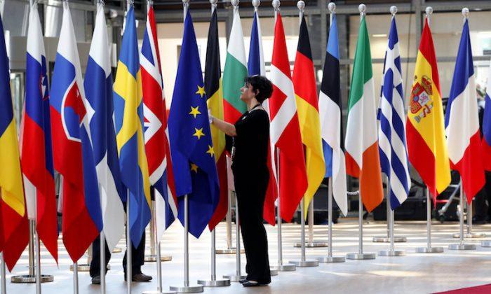 A woman adjusts flags ahead of European Union summit in Brussels, Belgium June 28, 2018.  (REUTERS/Yves Herman)