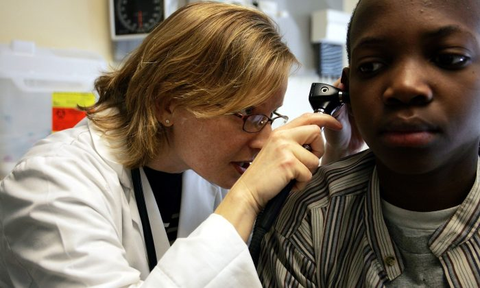 A doctor looks through an otoscope during an examination of a patient at the Codman Square Health Center in Dorchester, Massachusetts in this file photo. (Joe Raedle/Getty Images)