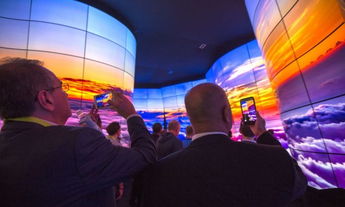 People walk through a display of LG OLED televisions at CES in Las Vegas, Nevada, on January 9, 2018. (David McNew/AFP/Getty Images)