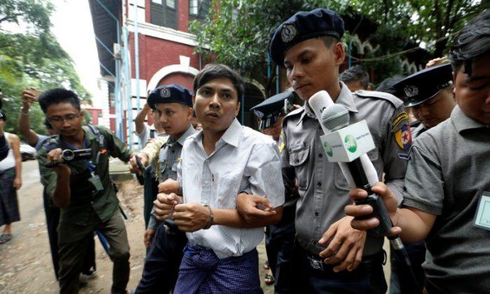 Detained Reuters journalist Kyaw Soe Oo is escorted by police while leaving Insein court in Yangon, Myanmar July 2, 2018. (Reuters/Ann Wang)