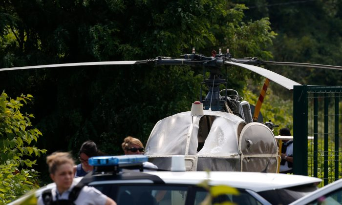 Police near a helicopter abandoned by French armed robber Redoine Faid after his escape from prison in Reau on July 1, 2018. (Geoffrey Van Der Hasselt/AFP/Getty Images)