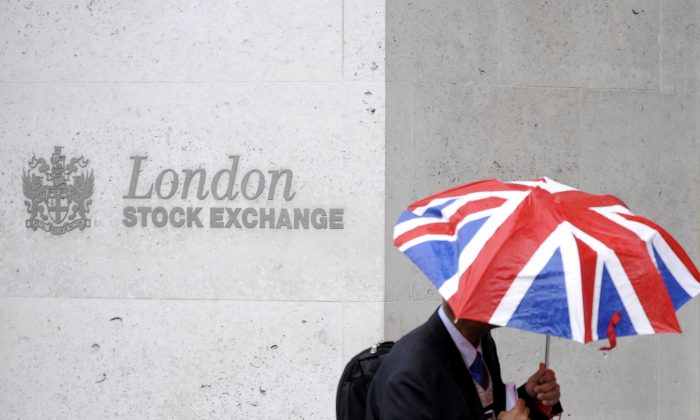 A worker shelters from the rain as he passes the London Stock Exchange in the City of London in this file photo. (Reuters/Toby Melville/File Photo)