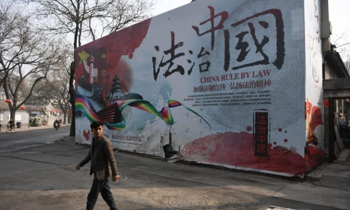 A security guard walks past a billboard with propaganda about rule of law in China on March 13, 2018. (Greg Baker/AFP/Getty Images)