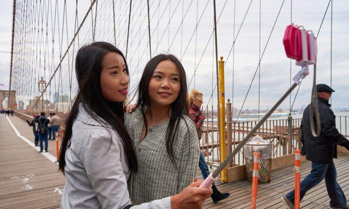Two Chinese women taking selfies on the Brooklyn Bridge in New York City in March 2016. (Sorbis/Shutterstock.com)