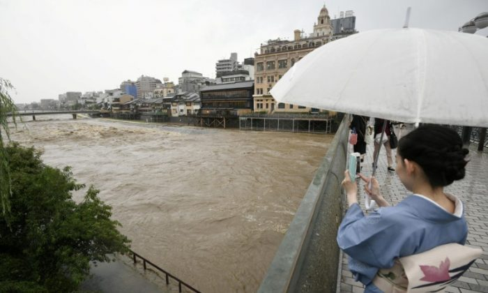 A kimono-clad woman using a smartphone takes photos of swollen Kamo River, caused by a heavy rain, from Shijo Bridge in Kyoto, western Japan, in this photo taken by Kyodo July 5, 2018.  (Mandatory credit Kyodo/via REUTERS)