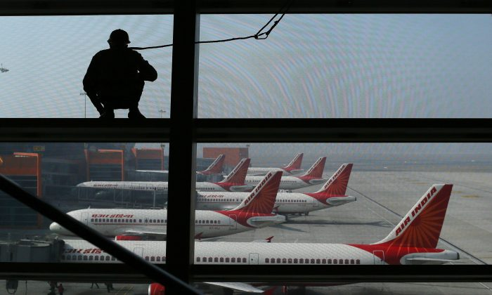 An Indian window cleaner stands on a beam overlooking Air India aircraft as they stand on the tarmac at Indira Gandhi International Airport in New Delhi on Nov. 17, 2012. (Andrew Caballero-Reynolds/AFP/Getty Images)