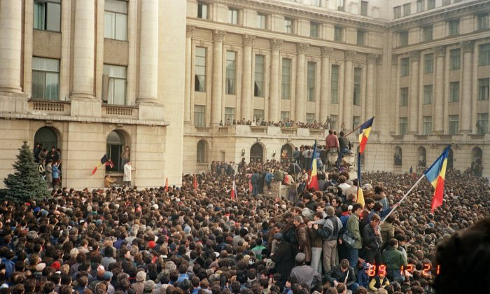 Bucharest citizens wave Romanian flags as they stage an anti-communist demonstration at the Republic Square on Dec. 21, 1989, shortly before the fall of the communist regime. (Photo credit should read AFP/Getty Images)