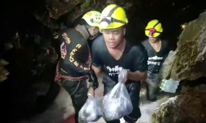 Rescuers carry supplies into the Tham Luang cave complex, where 12 boys and their soccer coach are trapped, in the northern province of Chiang Rai, Thailand, July 5, 2018. Video taken July 5, 2018. (RUAMKATANYU FOUNDATION/Handout via Reuters TV)