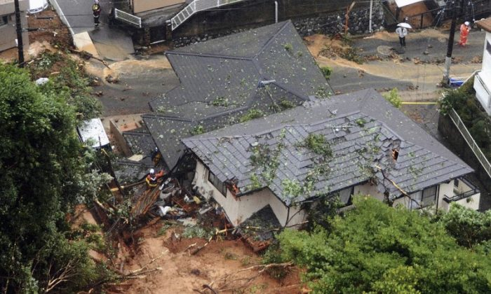 Rescue workers are seen next to houses damaged by a landslide following heavy rain in Kitakyushu, southwestern Japan, in this photo taken by Kyodo July 6, 2018. (Mandatory credit Kyodo/via REUTERS)