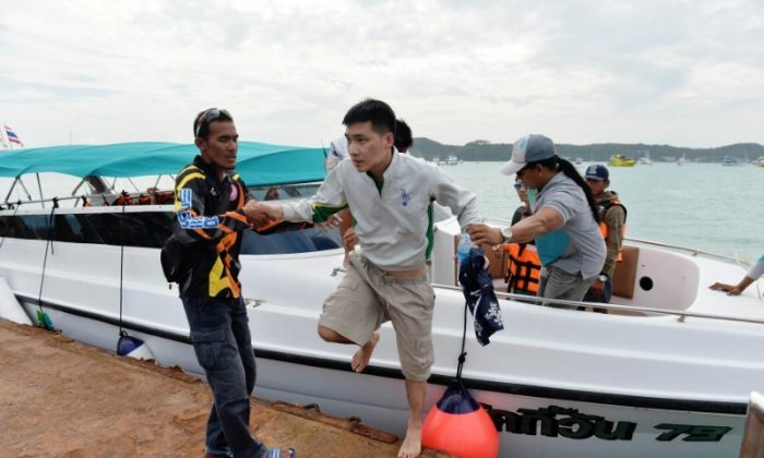 A rescued tourist is helped by rescue workers after a boat he was travelling in capsized off the tourist island of Phuket, Thailand, July 6, 2018. (REUTERS/Sooppharoek Teepapan)