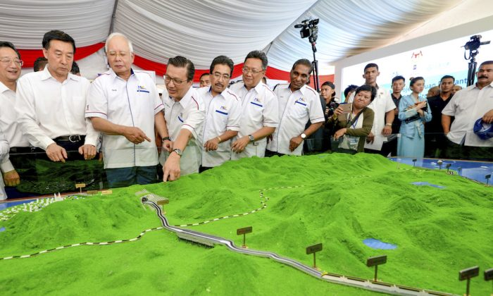 In Sept. 8, 2017, Malaysia former Prime Minster Najib Razak (3rd L) looks at modals of East Coast Rail Link during the project launching in Kuantan, Malaysia. (AP Photo)