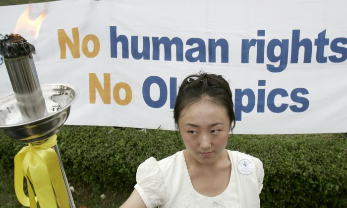 """A female activist holds up a torch, its flame a symbol for universal human rights, during an """"alternative"""" torch relay highlighting China's human rights record in Kuala Lumpur on May 25, 2008. The Human Rights Torch Relay, which protests China's hosting of the 2008 Olympic Games, highlighted the Chinese government's handling of the Tibet riots, the persecution of Falun Gong practitioners, and its ties with the Myanmar military junta, organizers said. (TENGKU BAHAR/AFP/Getty Images)"""