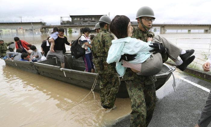Residents are rescued from a flooded area by Japan Self-Defense Force soldiers in Kurashiki, southern Japan, in this photo taken by Kyodo July 7, 2018. (Kyodo/Reuters)