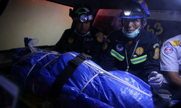 Thai Rescue workers sit next to the body of a victim on a stretcher, after a boat capsized off the tourist island of Phuket, Thailand, on July 7, 2018. (Reuters/Athit Perawongmetha)