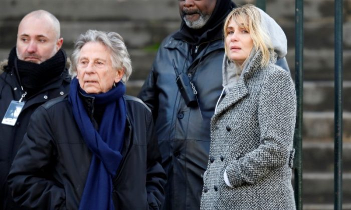 Film director Roman Polanski and Emmanuelle Seigner arrive at the Madeleine Church to attend a ceremony during a 'popular tribute' to late French singer and actor Johnny Hallyday in Paris, France, Dec. 9, 2017.  (REUTERS/Charles Platiau)